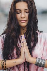 Young woman with closed eyes practicing yoga in prayer position