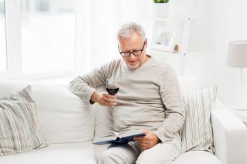 happy senior man drinking wine and reading book