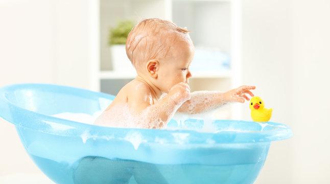 Happy toddler bathing in bathtub