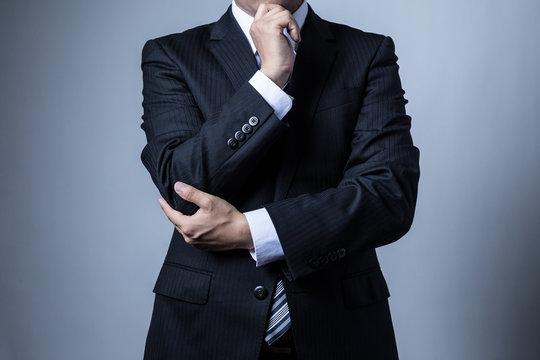スーツを着ているビジネスマン、考える
