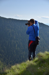 Photographer on a mountain peak shooting the landscape