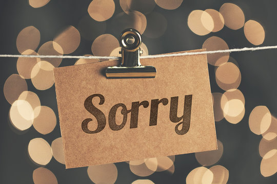 Sorry sign pegged to a string with blurred bokeh lights in the background