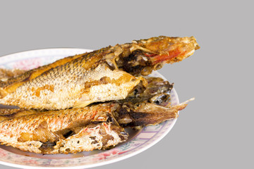 Fried fish is placed in a dish
