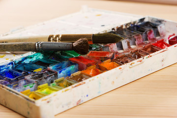 artists brushes and watercolour paints on palette. Vintage styli