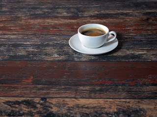 White cup of coffee on wooden old boards