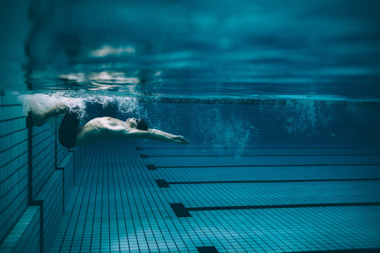 Male swimmer turning over in swimming pool