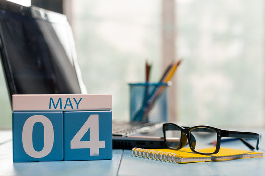May 4th. Day 4 of month, calendar on business office background, workplace with laptop and glasses. Spring time, empty space for text