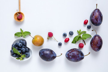 Fresh juicy berries and fruit on a white board.