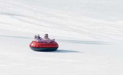 child riding on the tubing (inflatable sledges)