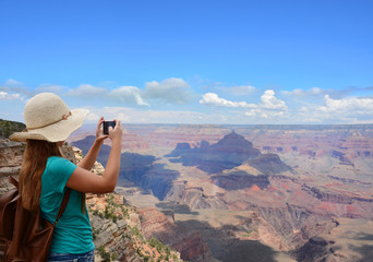 Girl taking photo of beautiful mountains with her smart phone on summer vacation hiking trip. Blue sky with clouds in the background. Grand Canyon National Park, Arizona, USA.