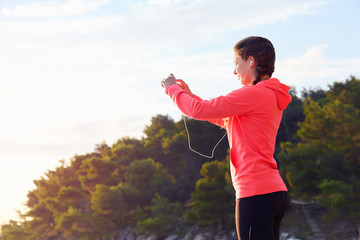 Active young woman listening to music during workout. Runner rests from routine exercise and makes photos. Happy jogger relaxing at the beach after run and looking at the sea.