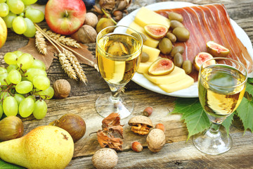 White wine, prosciutto, cheese and seasonal fruits on rustic table - (Delicious Mediterranean meal)