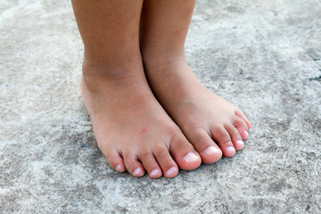Children feet on the concrete.