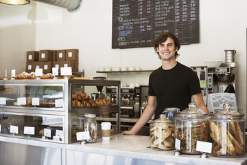 Portrait of happy man standing at store counter