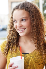 Teenage girl looking away while holding disposable cup