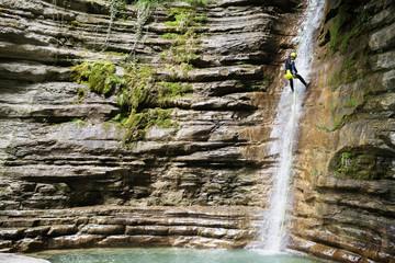 Woman rappelling down into lake