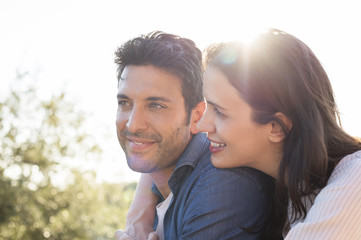 Side view of smiling couple against sky on sunny day