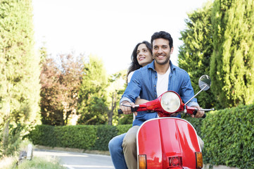 Smiling couple riding on motor scooter at park