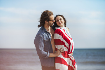 Side view of romantic man standing with woman wrapped in blanket at beach
