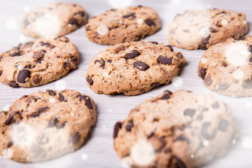 christmas concept - close up of chocolate chip cookies on wooden