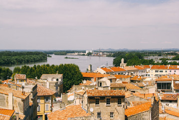 Rooftop view of the old town of Arles (France) with the Rhone river in the background.