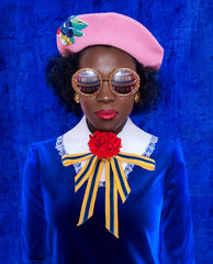 Woman wearing sunglasses, pink beret and blue dress, portrait