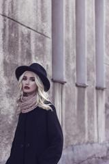 woman in hat walking in city