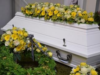 Weißer Sarg dekoriert mit vielen Blumen - Rosen, Gerbera, Lilien, Inkalilien in Gelb