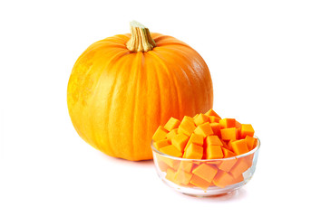 Glass bowl of sliced  cubes and whole pumpkin on white