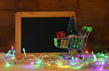 Shopping cart with christmas tree next to empty blackboard