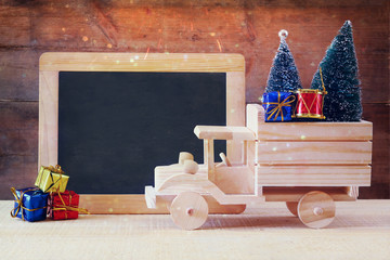 car carrying a christmas tree in front of empty blackboard