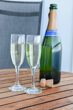 Champagne bottle with two filled glasses on wooden table. Celebration concept with sparkling white wine.