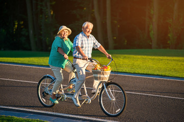 Senior couple rides tandem bike. Bicycle on the road. King of speed. Stay in motion.