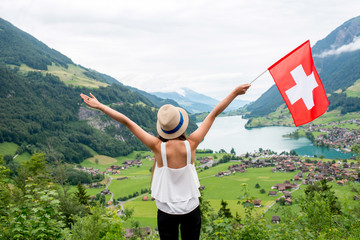 Young woman with swiss flag enjoying great landscape view on the valley with lake and village in Switzerland. Wall mural