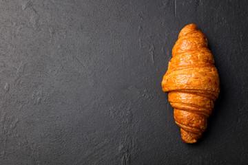 Fresh croissant on a black slate background.
