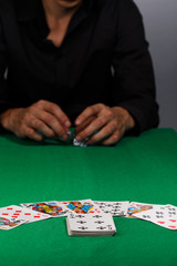 Gambling man in black shirt with dices in hands at playing table