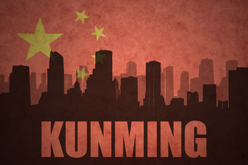 abstract silhouette of the city with text Kunming at the vintage chinese flag background