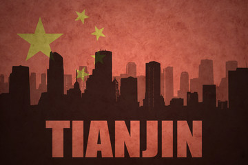 abstract silhouette of the city with text Tianjin at the vintage chinese flag background