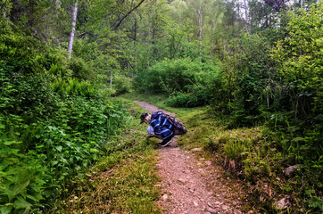 a young man in a green forest explores insects in the grass