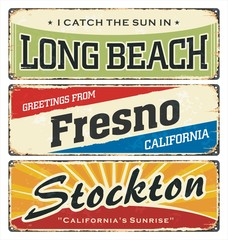Vintage tin sign collection with USA cities. Retro souvenirs or postcard templates on rust background. Vintage. Rust. Beach. America.