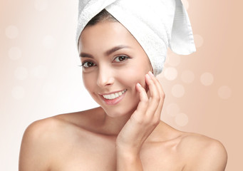 Young beautiful woman with towel on light background