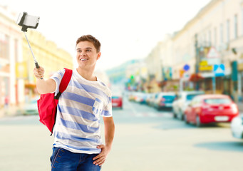 Young man taking selfie on blurred city street background.