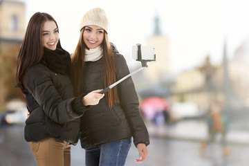 Young happy women taking selfie on blurred city street background.