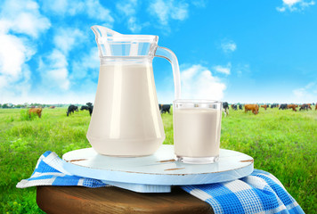 Glass of milk with napkin and cows on the meadow