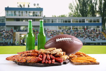 Rugby ball, snacks and bottles of beer on football field background