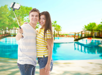 Young happy couple taking selfie on blurred swimmng pool background.