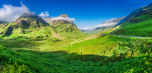 Stunning panorama in Glencoe at sunrise with shadow of man, Scotland