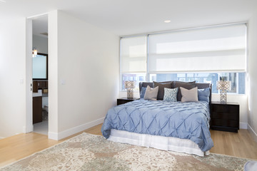 King Size bed with blue bed cover and pillows and large windows