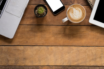 Office desk table with laptop, blank screen smartphone, blank screen tablet, leather notebook and cup of coffee.Top view with copy space.Office supplies and gadgets concept.