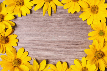 Frame of bright summer yellow flowers on wooden background. Greeting card. Place for design. Yellow petals.